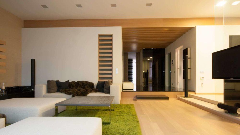 Вид из гостиной на распределительный холл, с лева камин и мягкая зона, с права стеклянный пилон и ТВ.